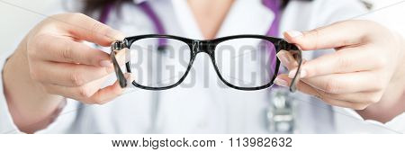 Female Oculist Doctor's Hands Giving A Pair Of Black Glasses