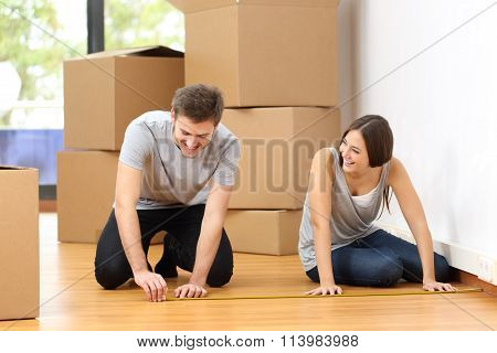 Couple Moving House And Measuring