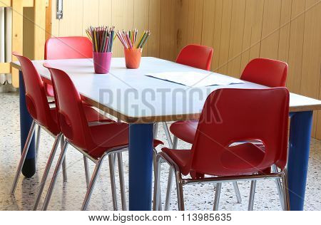 Desk Of A Nursery School With Pencils And Small Red Chairs