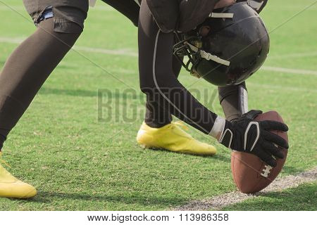 American football player setting up to snap the ball