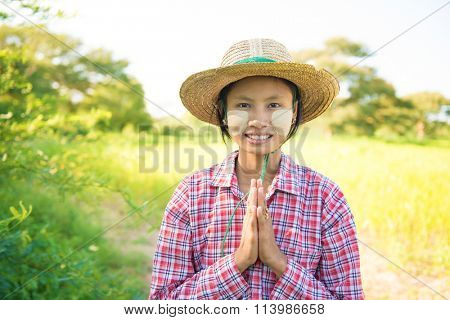 Portrait of a young Burmese female farmer with thanaka powdered face in blessing gesture.