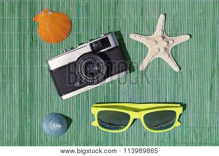 Starfish, retro camera, sunglasses, sea snail and sea shell on bamboo straw mat