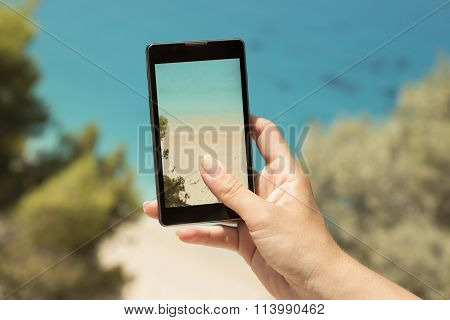 Taking a snapshot of a beautiful beach with a cellphone.