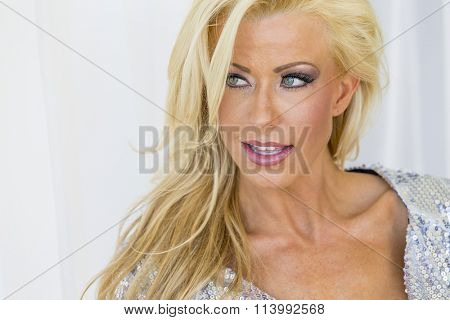 Attractive blonde model posing in an elegant evening dress