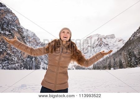 Woman Catching Snowflakes Outdoors Among Snow-capped Mountains