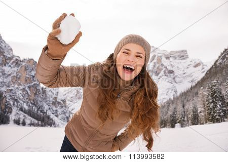 Woman Outdoors Among Snow-capped Mountains Throwing Snowball