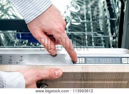 Man sets up a program on the panel of the dishwasher