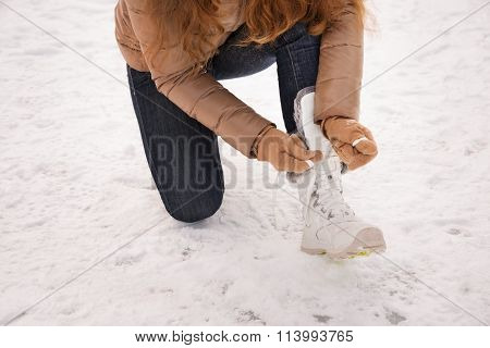 Closeup On Woman Tying Shoelaces In Gloves Outdoors