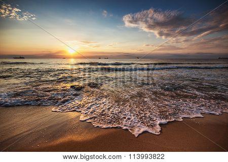Scenic Sunrise Over The Beach. Cargo Ships Sailing In The Sea