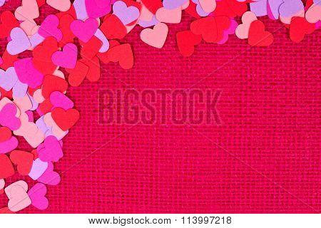 Paper Valentines Day hearts top corner border on pink burlap