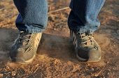 picture of stomp  - A person stomps on dirt causing dust to appear - JPG