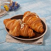 Постер, плакат: Two Croissant With Almonds On Blue Wooden Surface