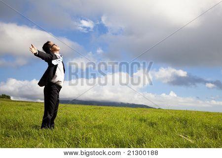 jovem em campo verde sob um céu azul