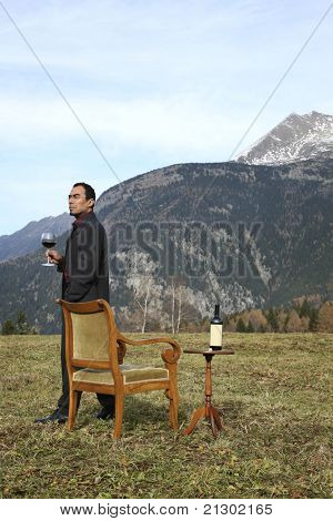 adult man red wine savors outdoors in the mountains