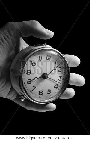 Left Hand and Old Alarm Clock