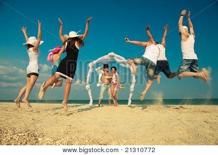 Noivo com noiva vestindo a lei, estando sob o arco na praia e os seus amigos saltando de alegria