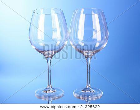 Dos copas de vino vacías sobre fondo azul