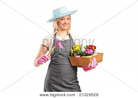 A young florist holding a mattock and flower pots isolated on white background