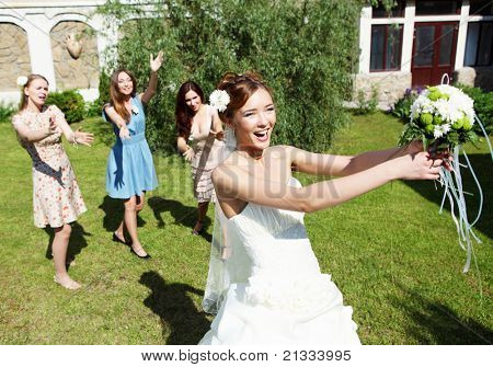 Young bride in white wedding dress throws a bouquet of flowers to bridesmaids