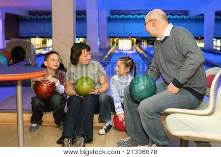 Family from four persons in rest and communicate in bowling club