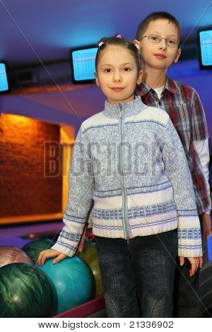 Brother and sister stand alongside near balls for bowling, focus on girl