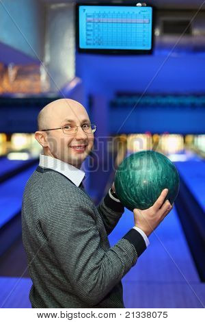 Man in glasses stands sideways and holds  ball for bowling