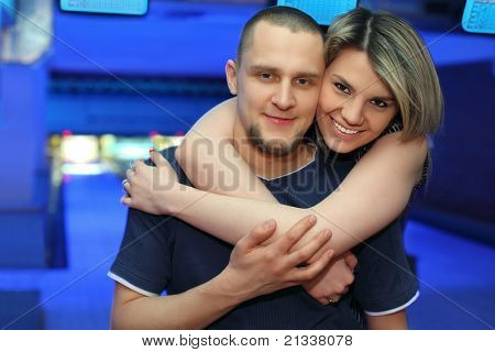 Girl hugs man and smiles during rest in bowling of club