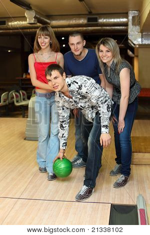 Man prepares throw  ball in bowling club and friends him encourage , focus on fellow in center