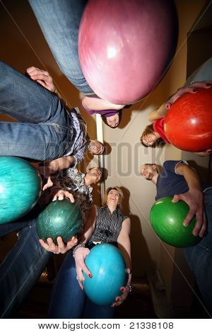 Girls and youths stand in circle and everybody hold ball for bowling and laughs