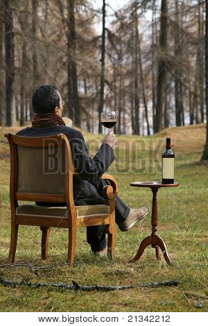 adult man savors the excellent red wine in the woods