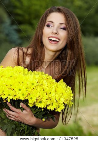 Young woman holding yellow flowers