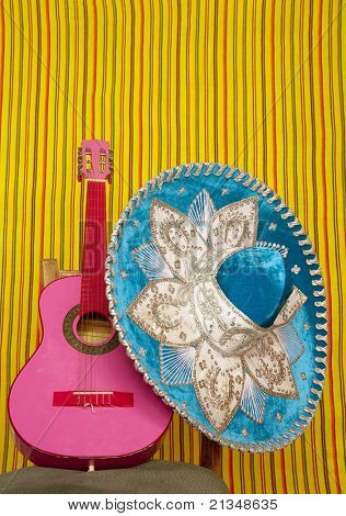 mariachi embroidered sombrero and pink guitar in striped mexican background