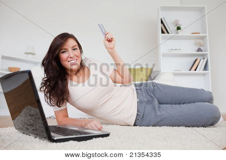 Attractive brunette female making a payment with a credit card on the internet while lying on a carpet in the living room
