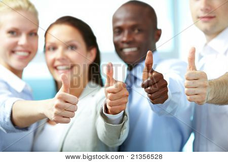 Four happy partners showing thumbs up