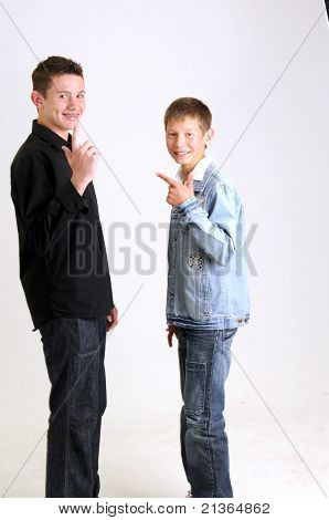 young attractive boys wearing blue jean jacket black shirt respectively waving and smiling