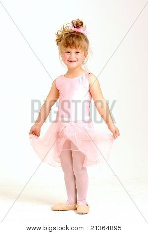 Little smiley girl wearing a pink ballet outfit is dancing holding her dress