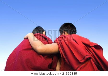 rear view of a monk holding another monk shoulder