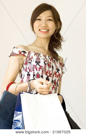 Beautiful asian woman in casual fashion carrying blank shopping bags ready for your logo or trademark