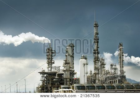 Oil refinery with smoke against moody sky