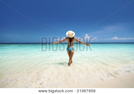 Young woman arms out enjoying the fresh air at beach