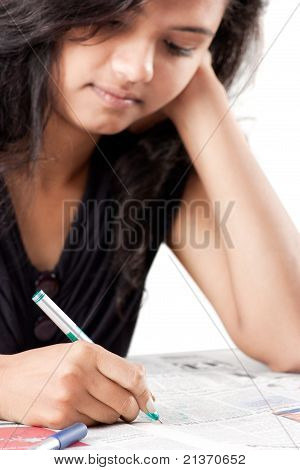 Tense beautiful indian girl writing on print paper
