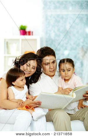 Portrait of happy family with two children spending time at home