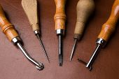 foto of leather tool  - Some tools to work leather over leather background - JPG