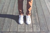 Fashion Hipster Cool Man With White Sneakers Close-up Stands On Wooden Floor poster