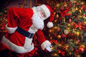 Santa Claus next to a beautiful ornate Christmas tree. Santa Claus dress up the Christmas tree. poster