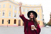 Happy brunette woman in hat and sweater waving away and glad to meet outdoors poster