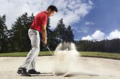Young male golf player in red shirt and grey pants chipping golf ball out of a sand trap with sand w