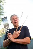 Mature man wields cooking utensils for a BBQ.