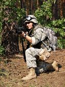 stock photo of hider  - Soldier wearing ACU in the woodland aiming the target with M4 carbine