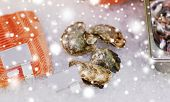seafood, sale and food concept - chilled fresh fish and oysters on ice at grocery stall over snow poster